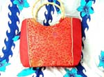 Wholesale womens accessory purse supply shopping. Red handbag has beautifully crafted gold colored oriental design on front and back